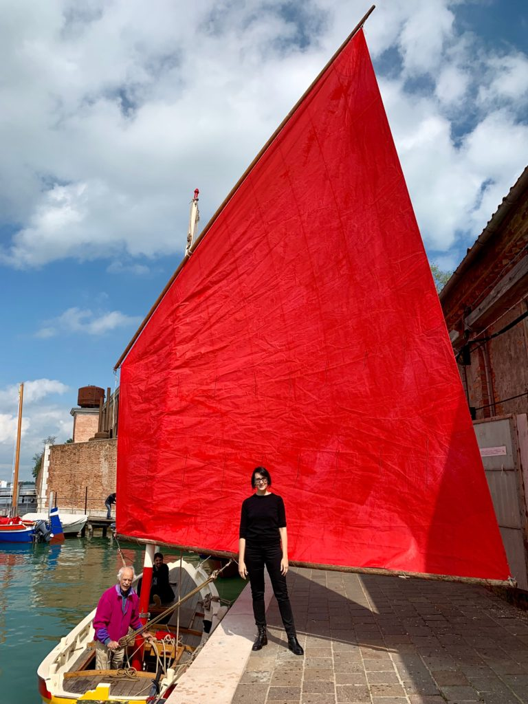 Melissa McGill with one of the boats for her project Red Regatta. Photo by Sarah Cascone.