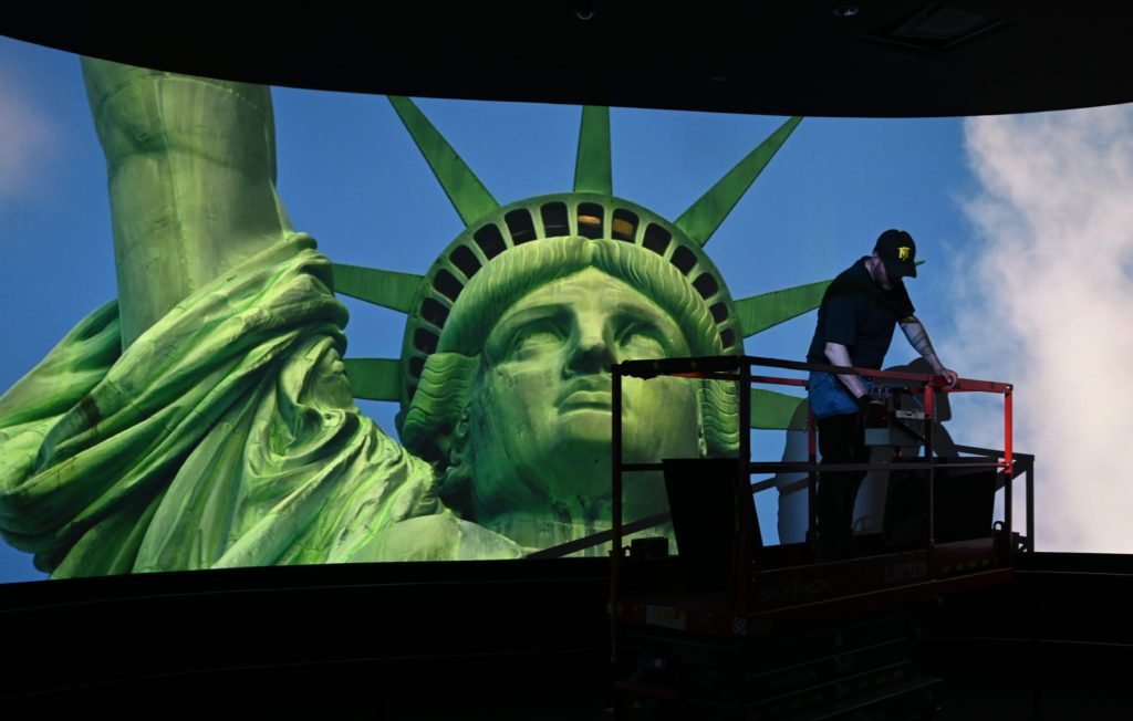 A worker puts finishing touches on the ceiling in a room showing a movie. Photo by TIMOTHY A. CLARY / AFP/Getty Images.