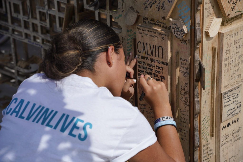 David Best, <em>Temple of Time</em> (2019). The artwork, which honors the 17 victims of the 2018 Parkland, Florida, shooting, was set on fire May 19, 2019. Here, a loved one leaves a tribute on the memorial. Photo by Nicole Craine, courtesy of Bloomberg Philanthropies.