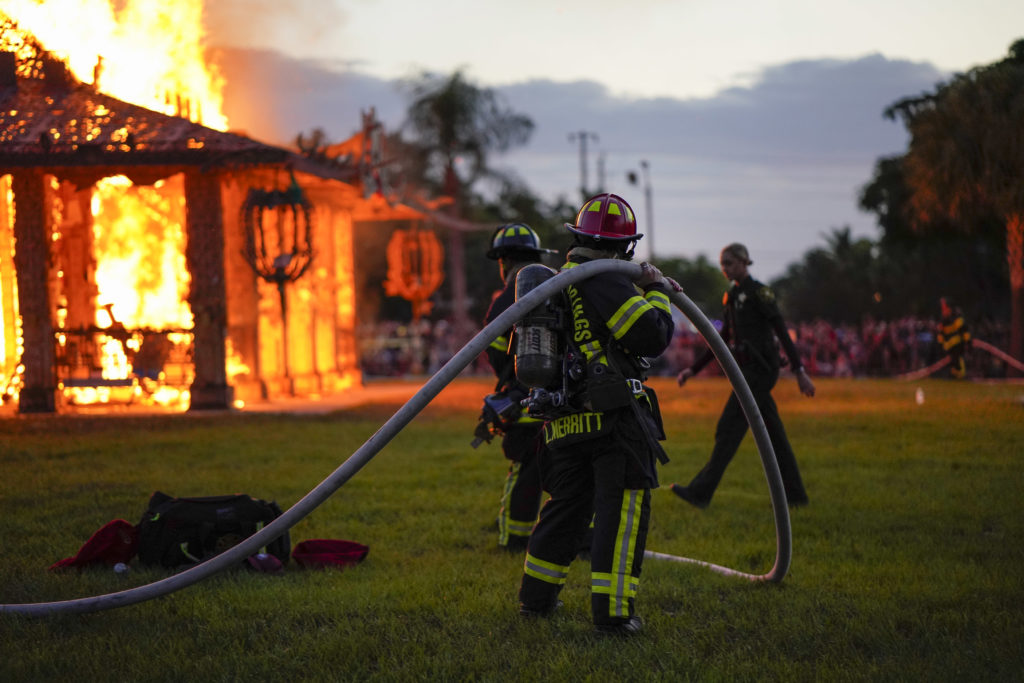 Firefighters monitor the flames as David Best's <em>Temple of Time</em> (2019), which honors the 17 victims of the 2018 Parkland, Florida, shooting, was set on fire May 19, 2019.  Photo by Nicole Craine, courtesy of Bloomberg Philanthropies.