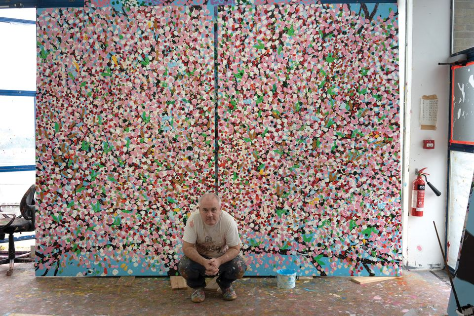 Damien Hirst with one of his new cherry blossom paintings. Photo by Prudence Cummings Associates ©Damien Hirst and Science Ltd.