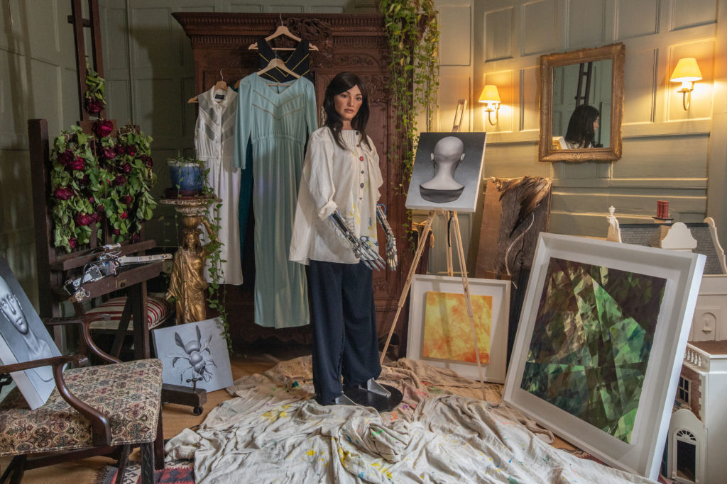 Ai-DA with Her Paintings. Photo by Victor Frankowski.