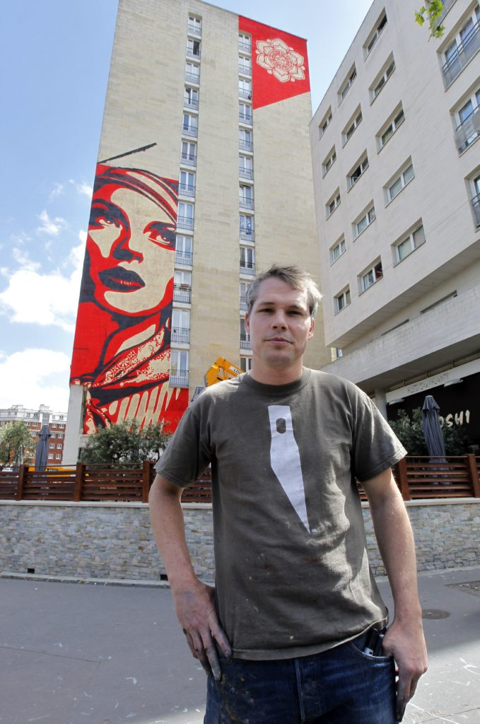 Shepard Fairey poses in front his work in Paris. Photo: Pierre Verdy/AFP/Getty Images.