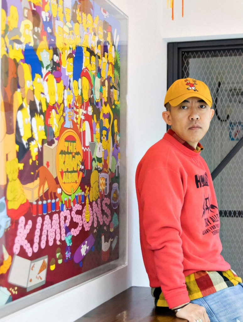 Collector NIGO with his KAWS painting THE KAWS ALBUM, which sold for $14.8 million at Sotheby's Hong Kong. Photo by Thomas Thompson, courtesy of Sotheby's.