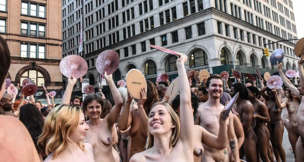 People celebrate after posing nude holding cut outs of nipples during a photo shoot by artist Spencer Tunick on June 2, 2019 in New York City. Photo by Stephanie Keith/Getty Images.