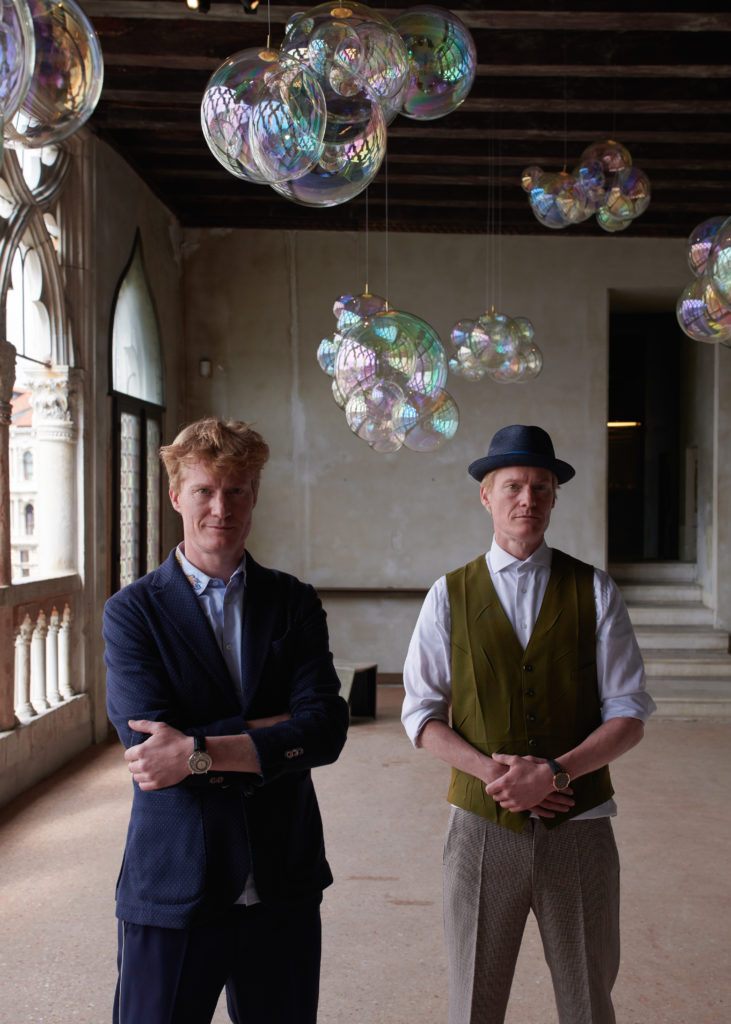 "The Verhoeven Twins next to their installation, ""Moments of Happiness"", in Venice. Image courtesy Piaget."