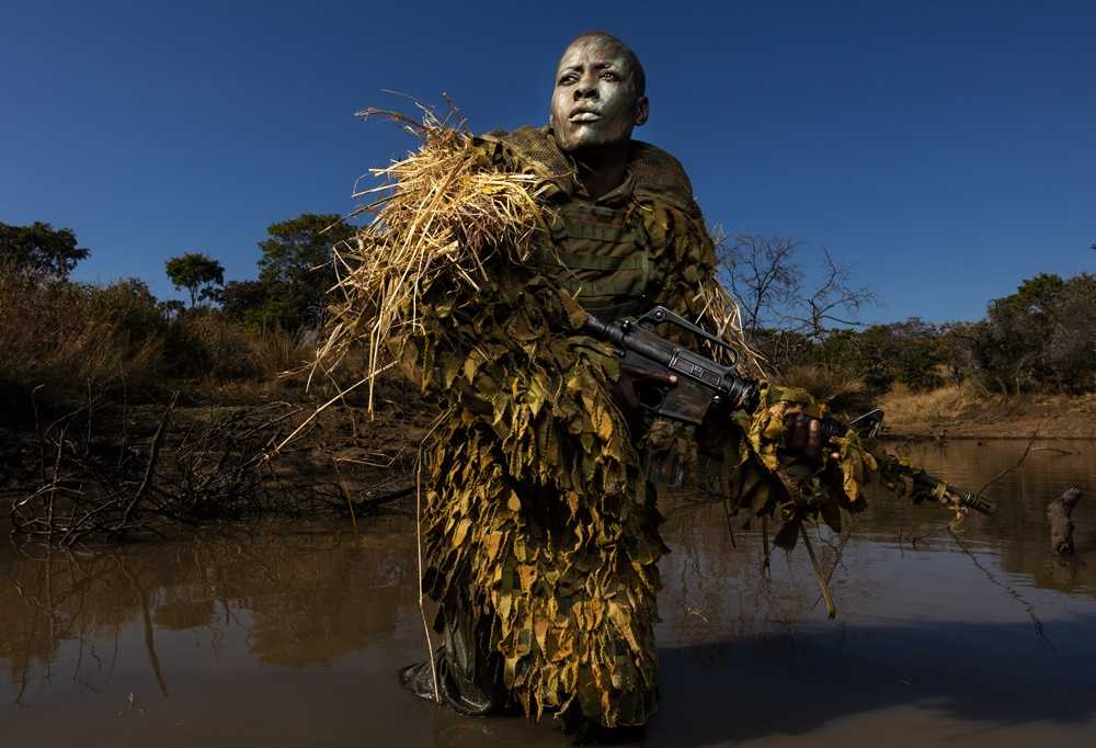 Phundundu Wildlife Area, Zimbabwe, June 2018: Petronella Chigumbura, 30, an elite member of the all female conservation ranger force known as Akashinga undergoes sniper movement and concealment training in the bush near their base. Photo by Brent Stirton, courtesy of Getty Images.