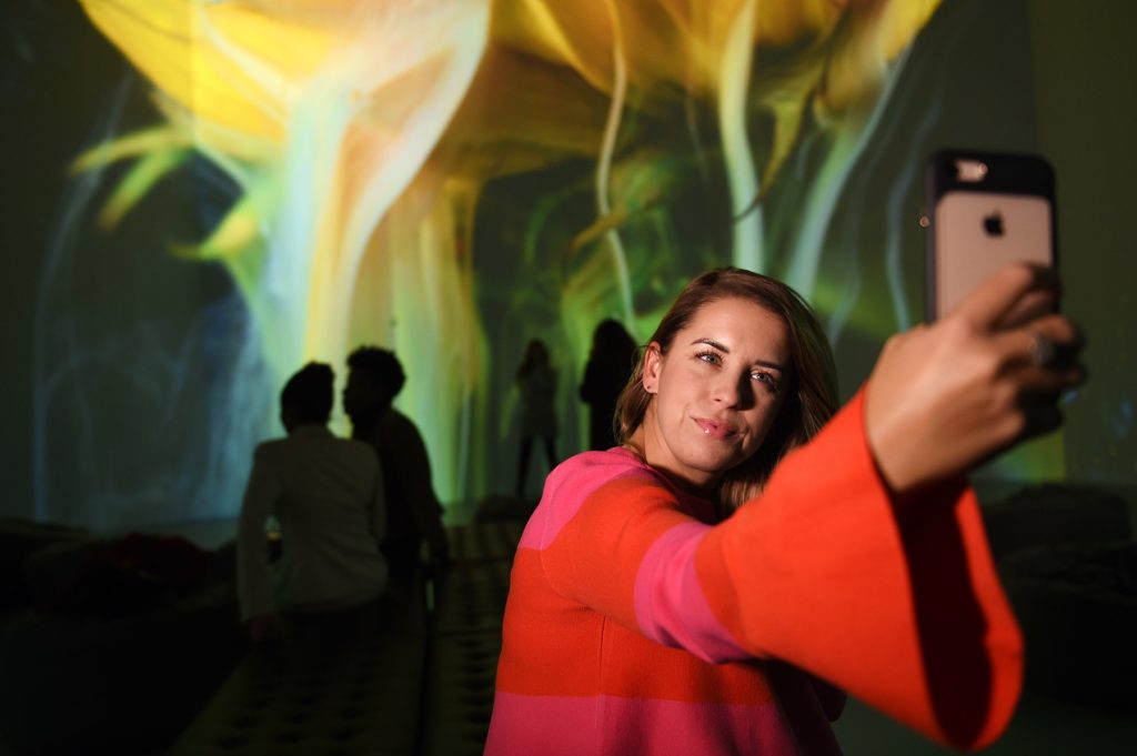 A visitor from Leesburg, VA, takes a selfie with her iPhone while visiting the Artechouse, in Washington, D.C., November 8, 2017. Photo courtesy Astrid Riecken For The Washington Post via Getty Images.