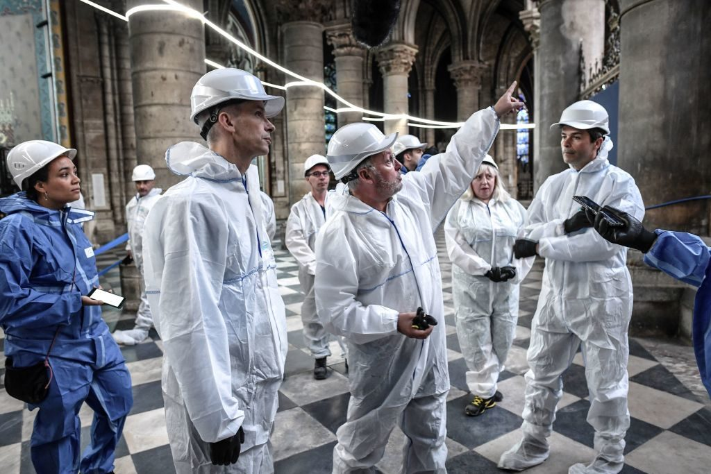 French Culture Minister Franck Riester (R) speaks with French chief architect of historical sites Philippe Villeneuve (L) as they visit the Notre-Dame de Paris Cathedral during preliminary work three months after a major fire. Photo by Stephan de Sakutin/AFP/Getty Images.