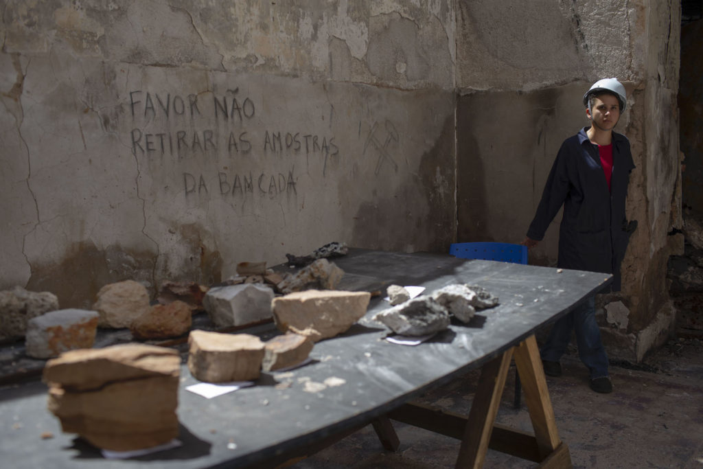 A worker guards artifacts found among the debris inside the National Museum of Brazil. Photo courtesy Mauro Pimentel/AFP/Getty Images.