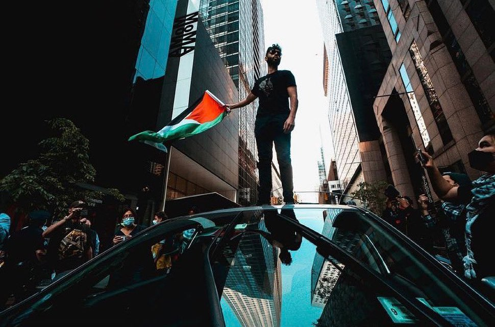 A demonstrator holding a Palestinian flag during a recent Strike MoMA protest. Courtesy of Strike MoMA via Twitter.